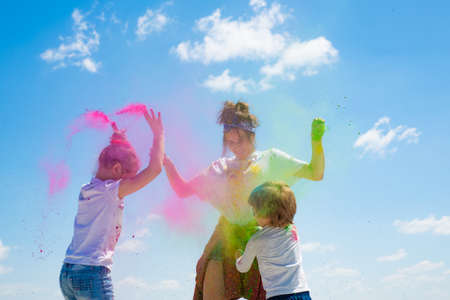 Emotional cheerful excited children with colored powder and color dust splash.