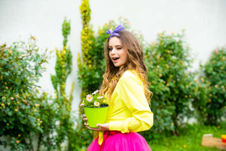 Young girl winking and planting flowers in pot. Working with plants. Summer farm. Spring village country. Cute girl with gardening tools.