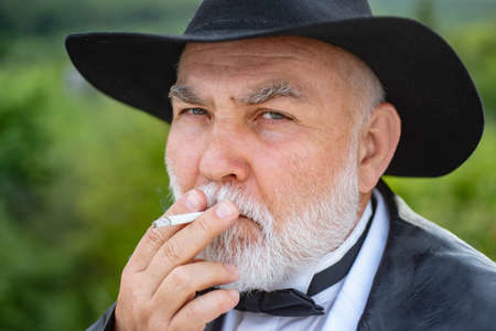 Old man smoking cigarette. Attractive elderly mature man. Face of senior fashion close up. Stockfoto