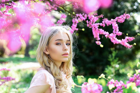 Spring bloom concept. Beautiful female face with perfect skin. Girl on dreamy face, tender blonde near violet flowers of judas tree, nature background. Beautiful Young Spring Woman.