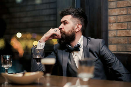 Bad dating. Confident man sitting at bar alone.