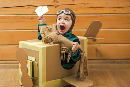 Baby boy playing with cardboard airplane on wooden wall background. Banque d'images