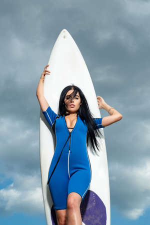 Lifeguard on beach. Saving life on sea. Sexy surfer girl with white surfboard.