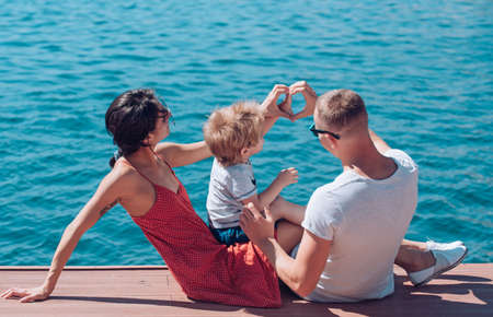 Happy family shape heart of hands at sea. Love and trust as family values.