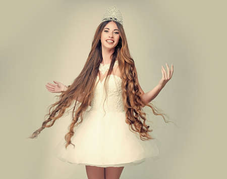 Woman with long hair with crown. Beauty salon and wedding fashion. Girl has fashionable makeup and healthy hair on grey background. Hairdresser and cosmetics.