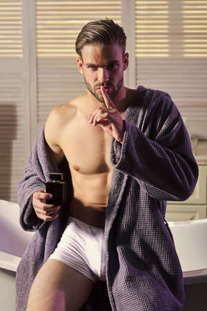 Man show silence finger gesture with perfume bottle, secret. Young attractive in bath robe in bathroom.