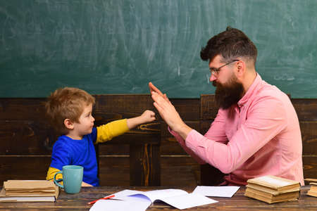 Father teacher and cute child pupil playing in classroom. Schoolboy achieving the task. Little champion salutation.