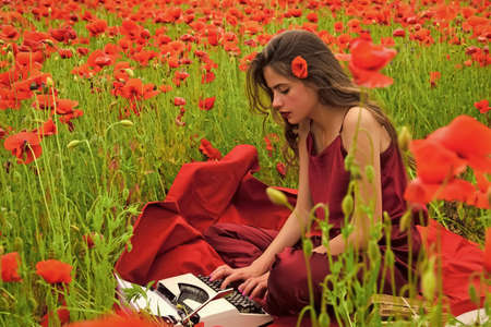 Woman with typewriter, camera, book. Poppy, Remembrance or Anzac Day. Woman writer in poppy flower field.