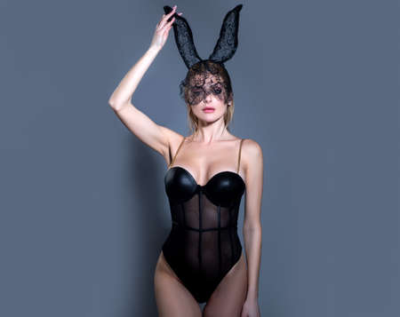 Sexy woman with bunny ears. Sensual lady posing in nice dress and black bunny mask.