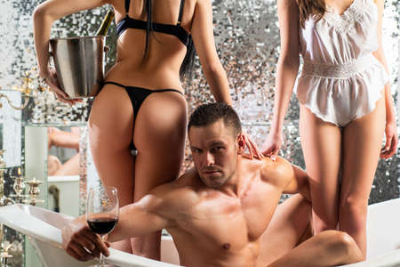 Luxury lifestyle. Rich man with girls. Polygamy love. Sexy women in bath. Sexual guy. Strong muscular man posing in bathroom.