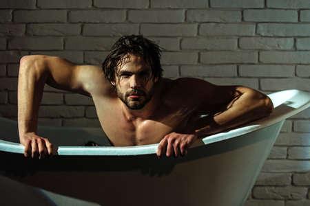 Sexy man in bathtub. Man with muscular body, in bath. Spa, bathing, hygiene and wellness guy.