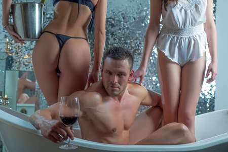 Sexy man in bath drink wine. Threesome concept. Three people in bathtub together. Swinger, orgy or trio in bath. Bisexual lady. Sexual fantasy.