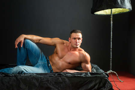 Portrait young men bodybuilder athlete, with a torso, lies on a bed in pillows in underwear.