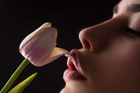 Female lips and spring flower. Sexy woman mouth and flowers. Oral sex, orgasm, blowjob, licking flower. Girl lips with tulips