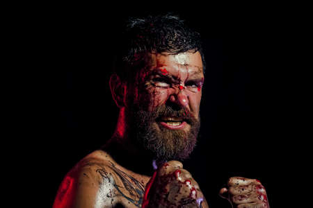 Angry man with blood paint on angry face. Hipster in fight position with fists on black background. Sport, boxing, fighting. Power man.