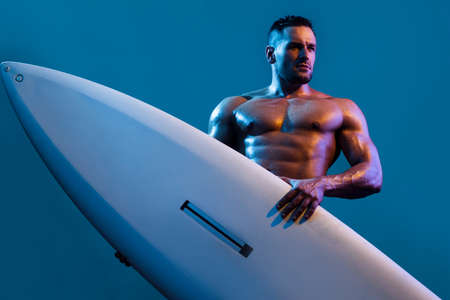 Guy on beach with surfboard. Young surfer man holding serf board. Summer vacation concept. Sexy muscular surfer with a surfboard. Summer boy, isolated on blue.