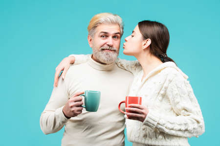 Happy couple at routine morning with cup of coffee or tea. Enjoying nice family cozy evening together. Young couple having a romantic moments. Standard-Bild
