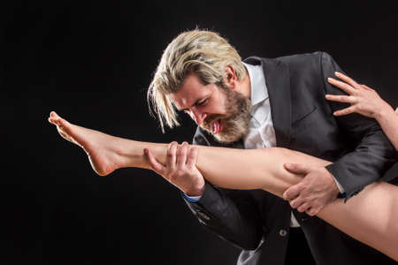 Strange bussinessman in suit licking female legs. Foot fetish. Luxury and patriarchy. Man lick leg.