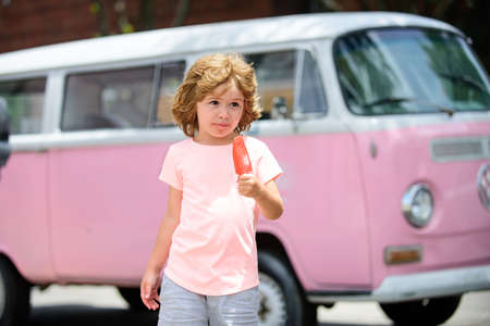 Beautiful little boy in a pink dress eating an ice cream.