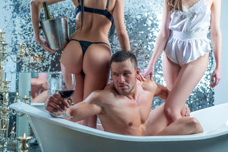 Sexy man in bath drink red wine. Polygamy love. Rich guy with girls in bathroom. Strong muscular male in bathroom.