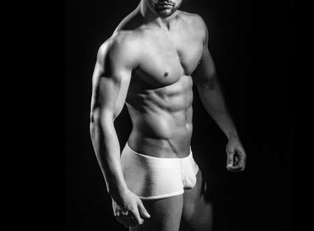Muscular man with body in pants. Sexy guy man with muscular torso. Undress on black.