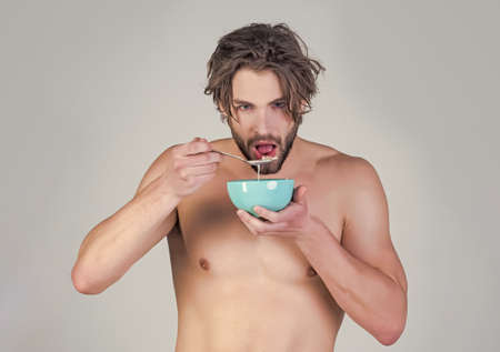 Man healthy eating. Sexy guy with muscular body eating cereal, healthcare. Food and beauty, health. Morning food Stock Photo