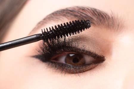 Closeup of eye makeup. Applying maskara on lushes Young woman getting make up with brush. Eyes visage woman.