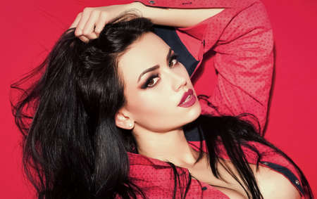 Fashion woman face. Beauty Fashion model girl. Fashion look. fashion model with long brunette hair and fashionable makeup on face has body on red background.