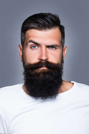 Handsome bearded man with long lush beard and moustacheon grey background.