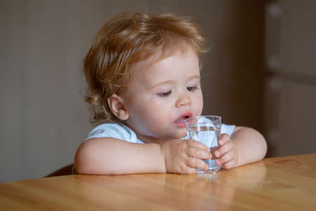 Healthy nutrition for kids. Baby drink water. Portrait of a sweet Beautiful child drinking a glass of water.