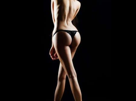 Back view of young woman in panties with beautiful body. Lingerie panties, bikini thong concept