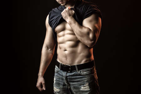 Sexy strong young man with muscular bodywith shirt on shoulder.
