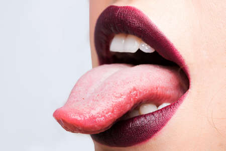 Female open mouth with lips purple lipstick and tongue
