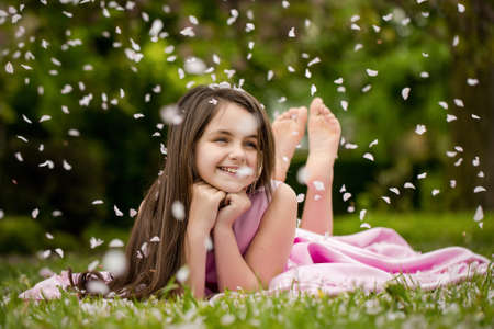 Beautiful little girl in pink dress with smiling face lying barefoot on green grass in spring flower blossom petals outdoor. Banque d'images