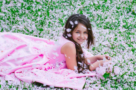 Beautiful little girl in pink dress with smiling happy face lying on green grass covered with spring flower blossom petals outdoor. Banco de Imagens