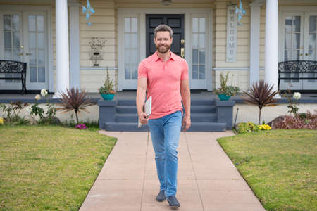Confidence and business concept. Man standing in front of his new home. Buy, sell, real estate, property, home insurance concept. Real people.