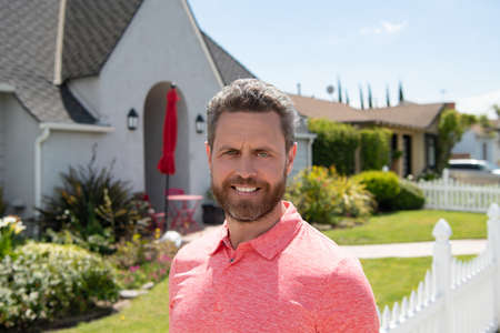 Happy man standing outside house. Business Concept. Portrait handsome businessman with confident face. Suburb background. Stock Photo
