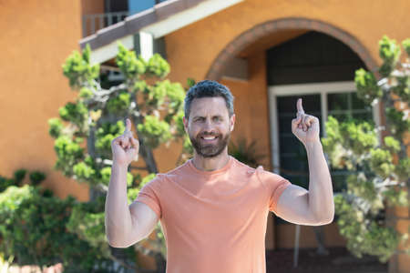 Portrait of happy real estate agent standing outside a house for sale. Realtor man waiting for visitors.