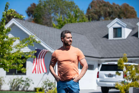 Man standing outside new american home. Handsome confident businessman in t shirt, looking up. Stock Photo