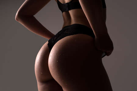 Sexy in lingerie. Huge buttocks. Female firm slim figure, bikini thong underwear. Woman silhouette body in panties. Butt with sensual touch.