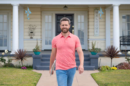 Portrait of middle-aged man satisfied with life success. Confidence and business concept. Businessman standing in front of his new home. Buy, sell, real estate, property, home insurance concept.