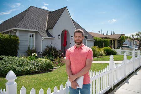Man businessman in front of house, outdoor. Portrait of a charming mature business man dressed in t shirt posing while new home and looking at camera. Stock Photo