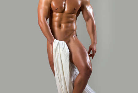 Sport guy with white towel. Sexy man with oily skin holds white sheet on grey background. Nude man or with muscle torso, male body. Standard-Bild