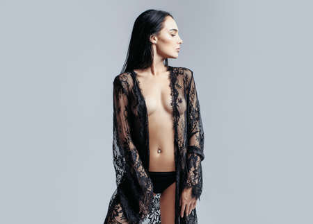 Sexy fashionable black lace dressing gown or bathrobe and panties. Naked girl or cute woman in fashionable black panties holds lace on dark background, has body and chest.