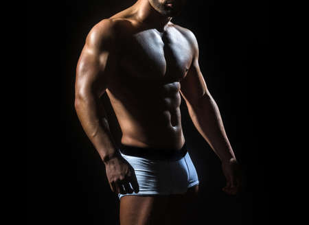 Sporty man with athlete body in pants. Sexy in white panties. Nude man or with muscle torso, male body. Foto de archivo