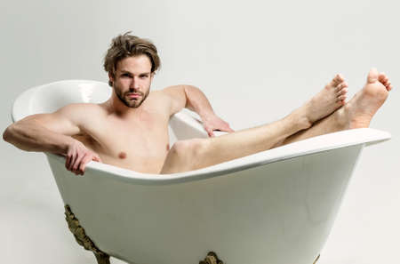 Sexy man with muscular torso sitting in bathtub. Sporty man takes a bath, isolated on white. Sensual gay.