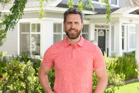 Man standing outside new home. Portrait of happy mature man looking at camera outdoor. Senior businessman feeling confident. Business man smiling with house in background. Stock Photo