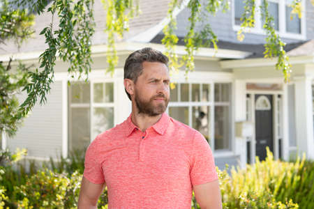 Man standing in front of his new home. Buy, sell, real estate, property, home insurance concept. Real people. Businessman standing outdoors during sunny summer day.