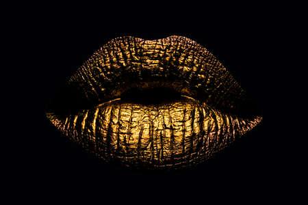 Abstract gold lips. Golden lips closeup. Gold metal art lip. Beautiful makeup. Golden lip gloss on beauty female mouth, closeup. Mouth Icon. Reklamní fotografie
