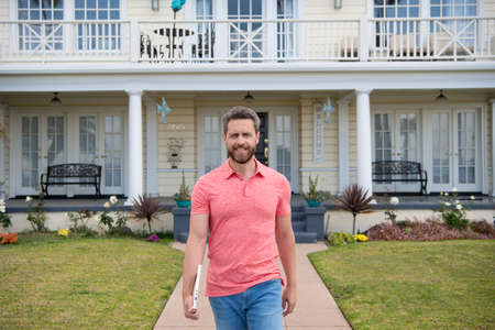 Portrait of confident real estate agent standing outside a house for sale. Realtor man waiting for visitors. Confidence and business concept. Portrait of charming successful entrepreneur in t shirt. Stock Photo